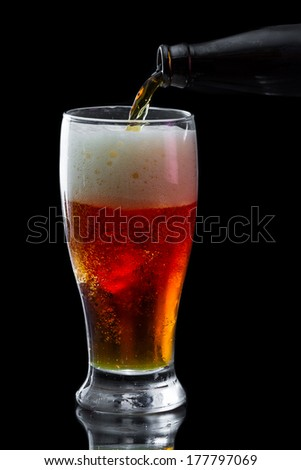 cold refreshing beer served in a cold glass isolated on a black background
