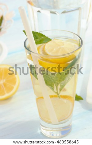Cold refreshing drink from fresh lemons and mint in glass on blue rustic table