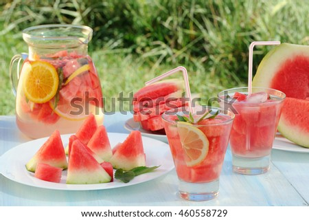 Cold refreshing drink from watermelon in a pitcher on wooden table in the garden