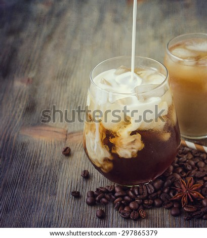 Cold refreshing iced coffee in glass with cubes of ice and pouring milk - stock photo
