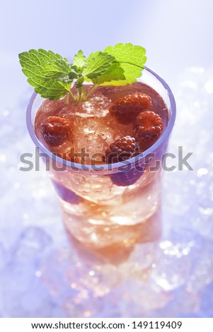 cold refreshment with raspberries, mint and soda on ice cubes  - stock photo