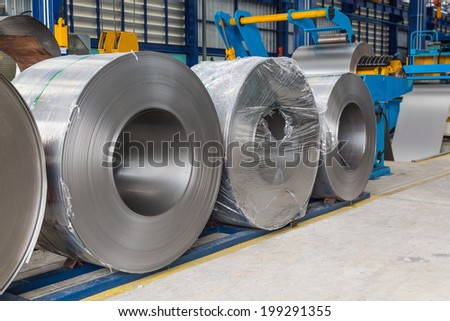 Cold rolled steel coils in storage area ready to feed to machine in metalwork manufacturing - stock photo