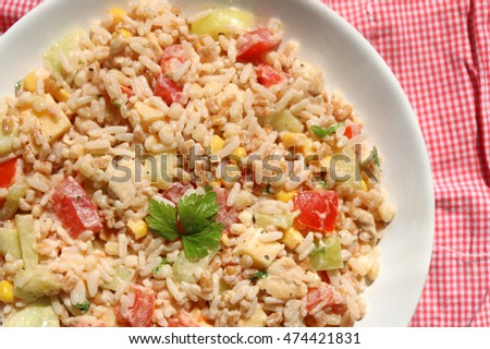 Cold salad with chicken, rice, various vegetables (tomato, pepper, cucumber, corn) and seasoning. Decorated with parsley leaves. Top view.