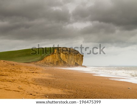 Cold sea surf on beach by Jurassic Coast cliffs and headland at West Bay in Dorset used as the location for the Broadchurch TV series - stock photo