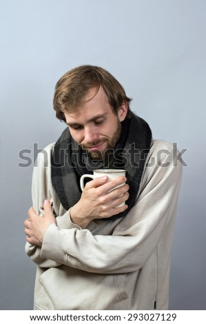 Cold, sick man dressed in grey sweater holding a cup of tea in hands isolated on grey background