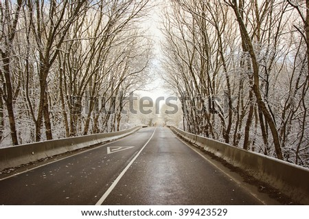 Cold snow covered road in winter landscape