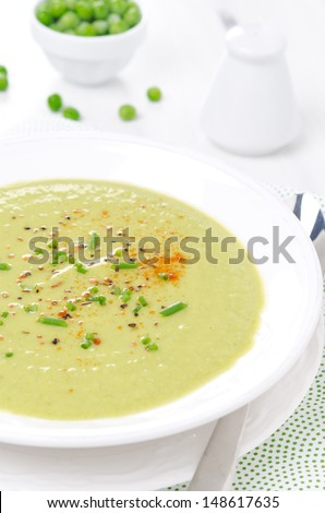 cold soup of green peas with yogurt, chives onions and peppers, vertical close-up