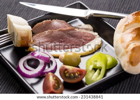 Cold starter, with smoked ham, liver bon-bon, and greaves  decorated on plate with vegetables and bread