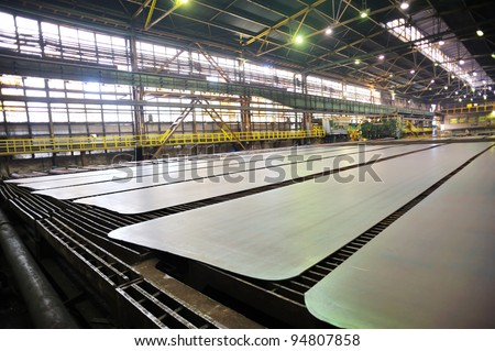 Cold steel plate on conveyor - stock photo