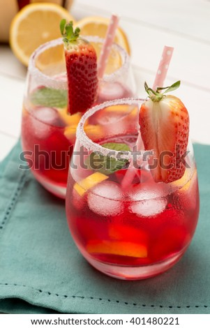 Cold strawberry drink with fresh strawberries and lemon on wooden background