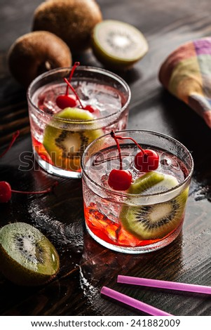 Cold summer cocktail drink with red cherry and kiwi - stock photo