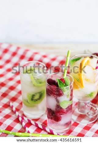 Cold summer cocktails with strawberries, kiwi, orange and mint in steklyannmyh glasses. Drinks and fruits on a rustic tablecloth. - stock photo