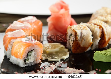cold sushi on black dish and white background - stock photo