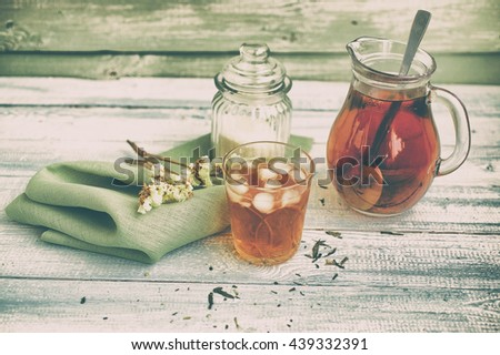 Cold tea on a wooden background. Ice tea. Cold drink. Vintage toning