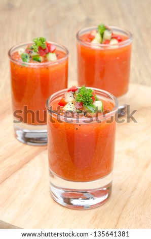 cold tomato soup gazpacho in portion glasses on a wooden board - stock photo