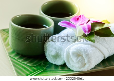 cold towel and tea cup on the tray at spa area - stock photo