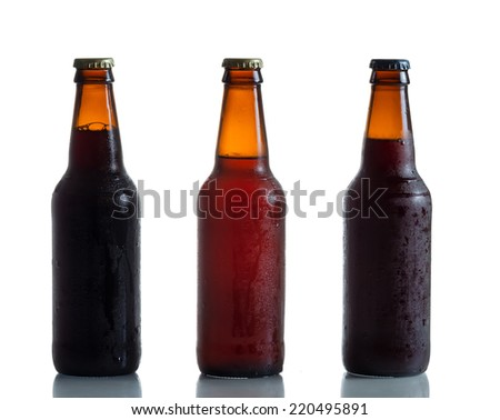 Cold unopened dark and amber beer bottles on white with reflection  - stock photo