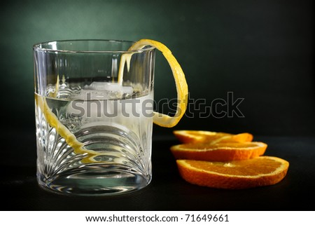 Cold vodka in a glass, with decor oranges and lemon, in black green background, part of art beverage background