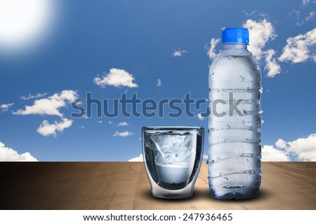 Cold Water Bottle and Glass Of Ice Cubes on Wood Table With Blue Sky Background - stock photo
