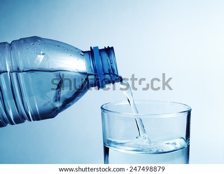 Cold water bottle pour water to glass with shallow depth of field - stock photo
