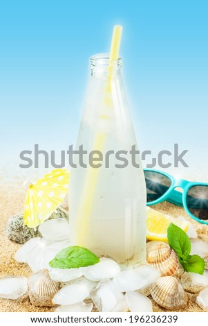 Cold water in a bottle with ice cubes on sand background - beach bar summer holiday cold beverages menu. Layout with free text space. - stock photo