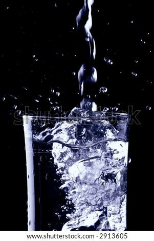 Cold water pouring into a drinking glass - stock photo