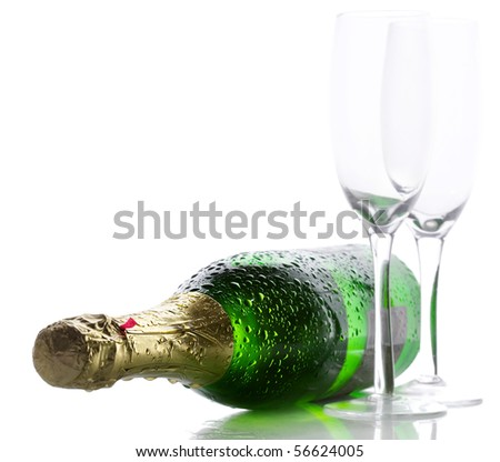Cold wet bottle of champagne with two empty glasses - stock photo