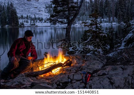 Cold winter night and man warms at campfire - stock photo