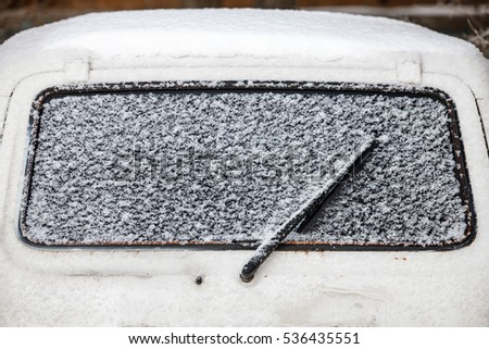 Cold winter. The car window under the snow