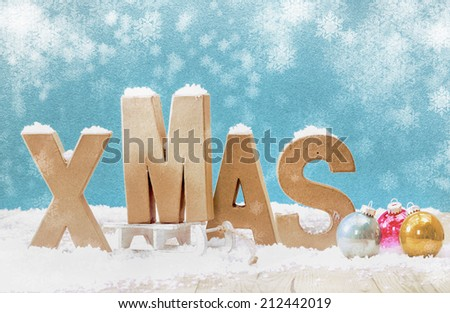 Cold wintry Xmas background with wooden letters for Xmas in snow with colorful Christmas baubles under falling snowflakes on a cool blue background with copyspace - stock photo