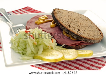Coleslaw and pickles accompanying a deli sandwich. - stock photo