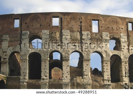 Coliseum wall with arcs and blue sky - stock photo