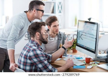 Collaboration is a key to success. Three young business people discussing something while looking at the computer monitor together  - stock photo