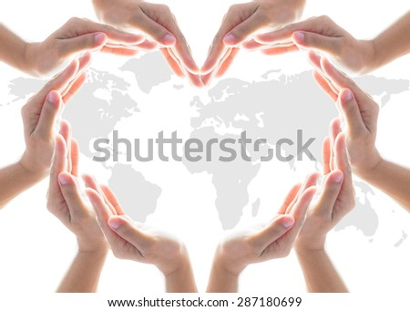 Collaborative human hands grouped in heart shape on world map background: International cooperative, charity aid, friendship and world protection CSR concept: Teamwork and caring idea concept/ aim    - stock photo