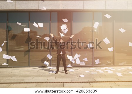 Collage of businessman posing in full length on street with his arms raised. Handsome freelance man in black business suit. Many sheets of paper are around. Toned picture. - stock photo