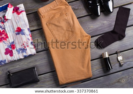 Collage of modern men's clothing on a dark wooden background. - stock photo