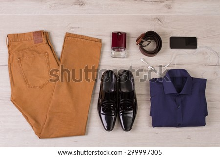 Collage of modern men's clothing on a white wooden background. - stock photo