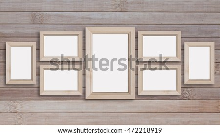 Collage of seven blank wooden photo frames on wooden panels wall.