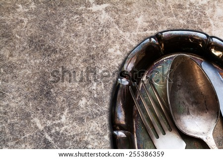 Collage: Tableware set on the vintage silver tray. spoon, knife and fork. vintage book cover background. scratches and scrapes. Soft focus. - stock photo