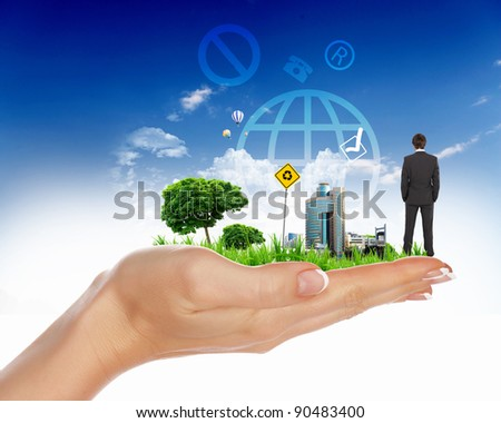 Collage with a human hand holding a green landscape - stock photo