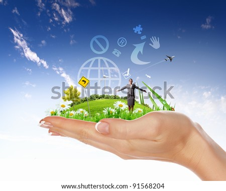 Collage with a human hand holding a green landscape