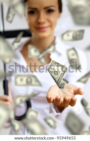 Collage with business woman under money rain with umbrella - stock photo