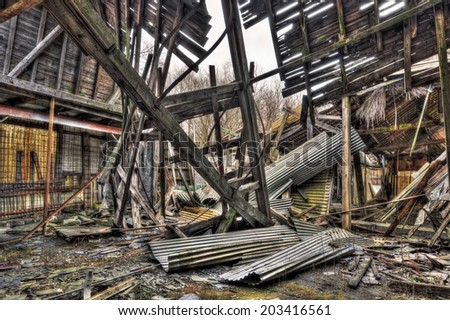 Collapsed roof of tumbledown warehouse, HDR - stock photo