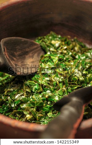 Collard greens in a wooden bowl with spoons. - stock photo