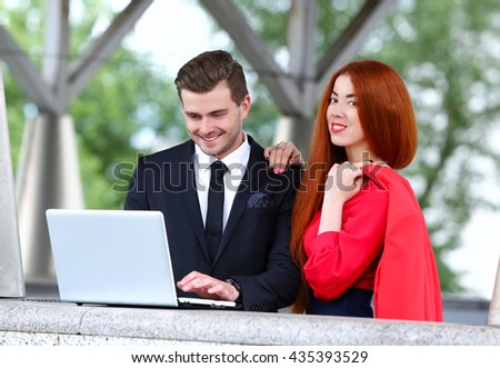 colleagues at work man and woman looking at a laptop, discussing project - stock photo