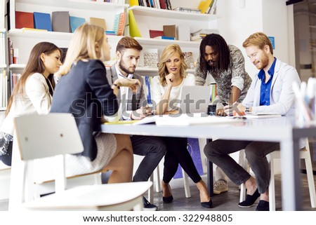 Colleagues brainstorming in office while pointing out new ideas on laptop - stock photo
