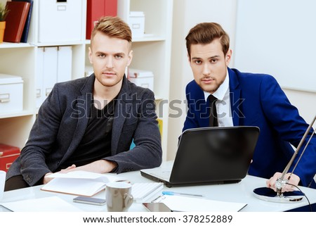 Colleagues businessmen discussing working issues at the office. - stock photo
