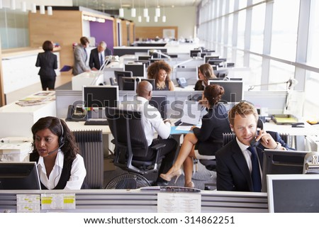 Colleagues busy working at desks in an open plan office - stock photo