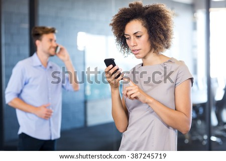 Colleagues communicating on mobile phone in front of conference room in office - stock photo