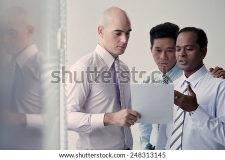 Colleagues discussing business document in the office - stock photo